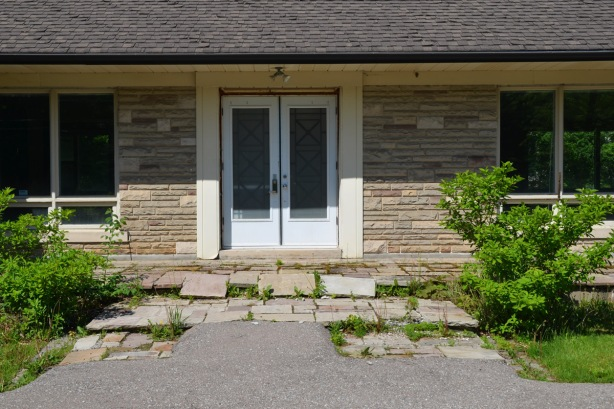 nonsdescript white double doors as front entranceway of a house, flagstone steps and porch are buckling as is the ashphalt walkway leading to the front door.