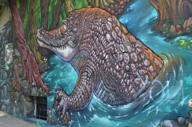 part of a large colourful mural by clandestinos smoky and shalak - a crocodile or alligator coming out of the water