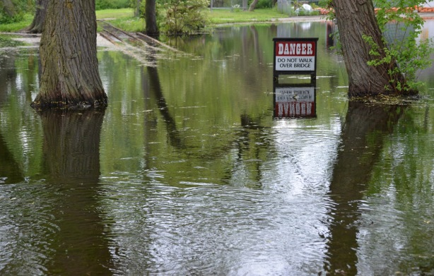 a sign says danger stay off the bridge, sign is sitting in a pond of water caused by clooding of Centre Island, train tracks from the amusement park train ride are partially under water too