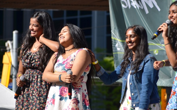 four female singers are smiling, they've just finished a song, performing at Yonge Dundas square as part of Desifest, all 4 are of South Asian descent