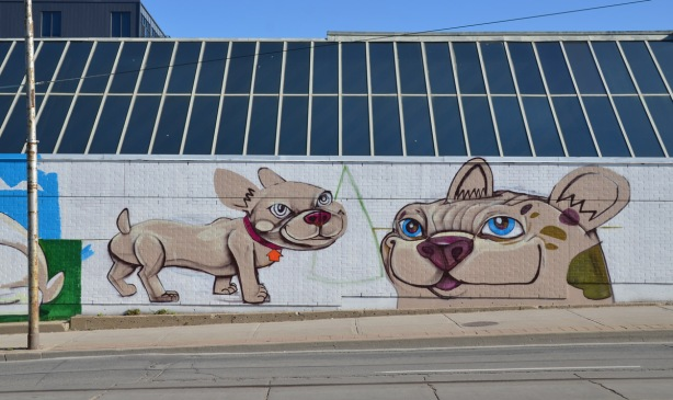 two dogs painted on a mural that isn't quite finished, on the side of a building,