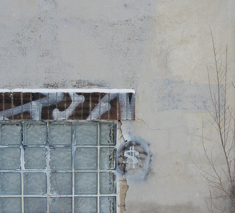 grey concrete wall with window, someone has drawn a dollar sign on the wall, leafless shrub growing against the wall, winter time