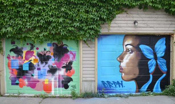 a mural on a garage door in an alley, part of butterflyways project - two adjacent garage doors, the left one is width=