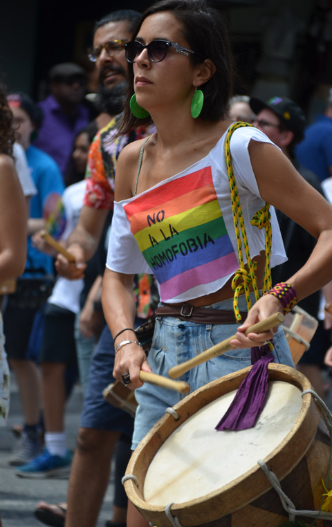 a woman drummer, She is wearing a tshirt that says no a la homofobia. walking in dyke march