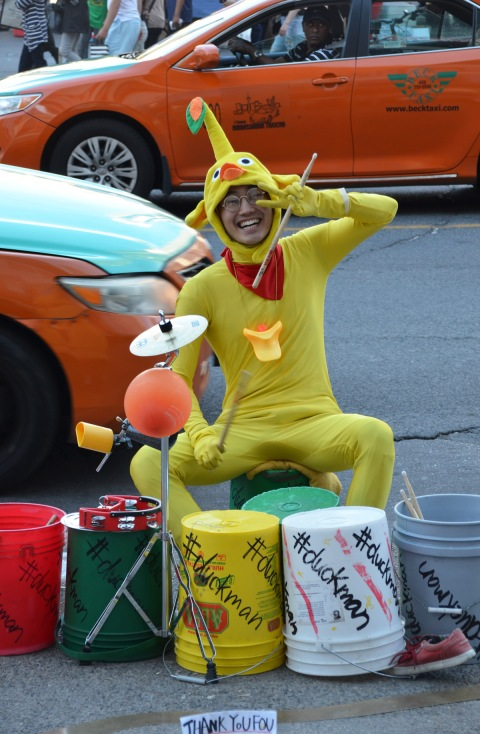a young Japanese man is dressed in a yellow body suit, seated on a stool on the sidewalk on Yonge Street, he is playing the drums - actually 5 empty plastic upside down buckets, with #duckman written on the buckets