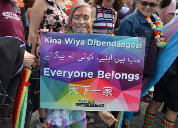 a girl holds up a sign from the East Enders Everyone belongs, that has the expression everyone belongs, written in an indigenous language as well as arabic and chinese (or other Asian language)