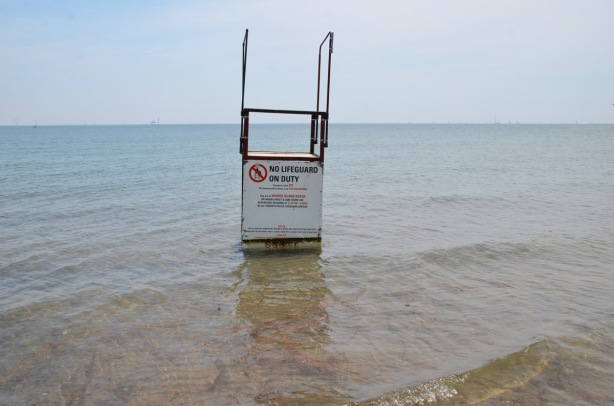 an empty lifeguard station on a flooded beach. it is in the water of Lake Ontario and is surrounded by water