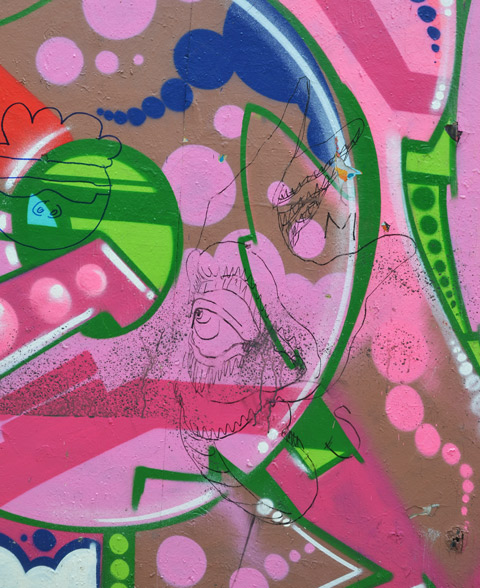 on top of pink and green abstract swirly street art, a drawing in black marker of a hand, with a face (eye and mouth) coming out of the back of the hand.