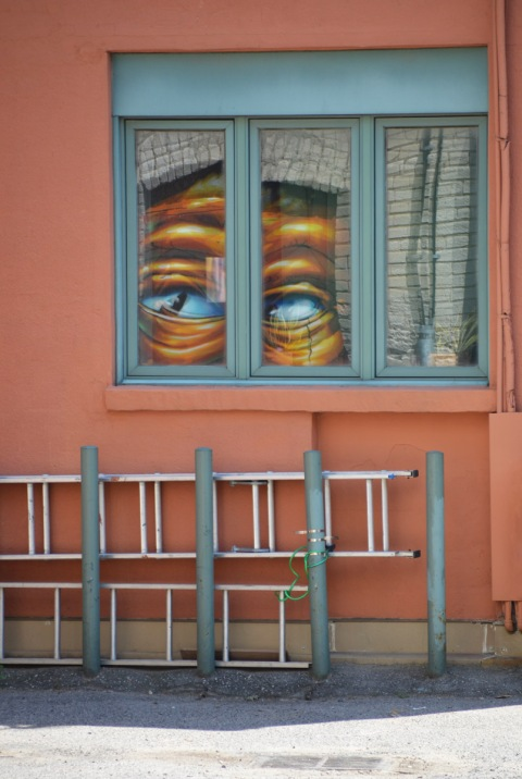 an orange, or salmon, coloured wall with a window. in the window is a reflection of a pair of eyes from a large street art mural. under the window are two ladders lying horizontal.