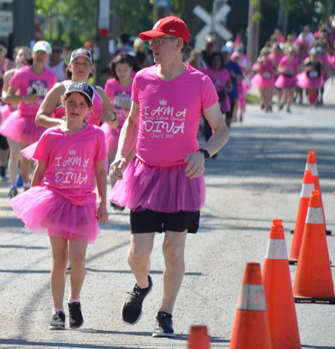 a father and daughter, both in pink tutus run in a 5k race, Run Like a Diva, other runners in the background