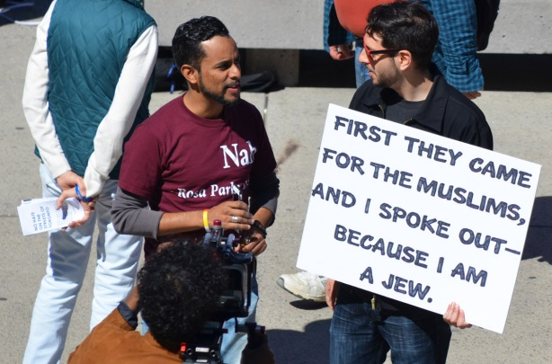 two men talking at a protest rally. one holds a sign that says First they came for the muslims and I spoke up because i'm a Jew