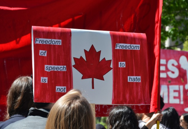 a protest sign in the shape and design of a Canadian flag on the red stripes are words that say Freedom of Speech is not Freedom to hate