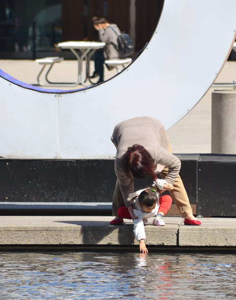 a mother helps her young daughter reach down and touch the water in the fountain at Nathan Phillips square
