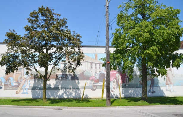 two trees obscure a faded mural