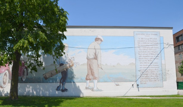mural of two men golfing. One is swinging a golf club and the other has a golf bag slung over his shoulderh