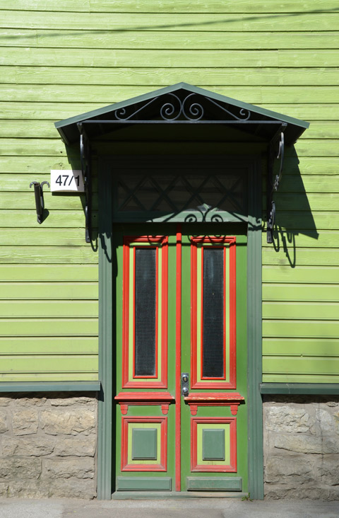 front door of a house in Tallinn Estonia, wood - green wood house with double doors with red and yellow trim on the two tone green door