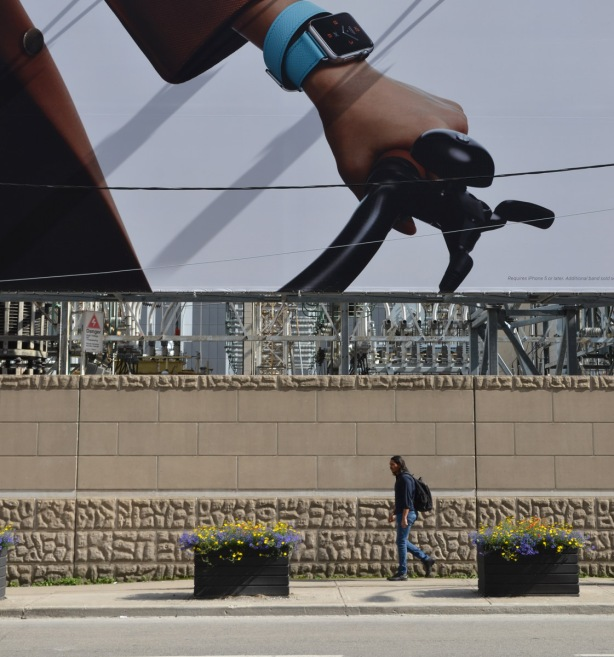 a man walks on the sidewalk below a largef ad for Apple watches.  The photo is cropped so that the only part of the ad that shows is a hand on the handle bar of a bike.  A bright turquoise watch is on the person's wrist