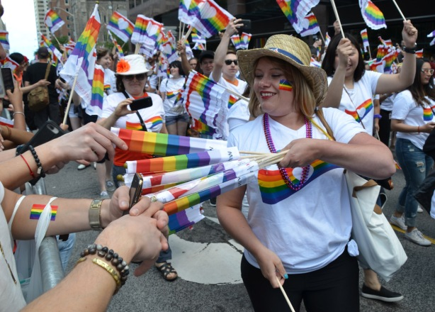 a woman in a white t shirt with rainbow on the front, and a straw hat is passing out rainbow flags to the crowd. others in the parade behind her are doing the same, others are waving the flags.