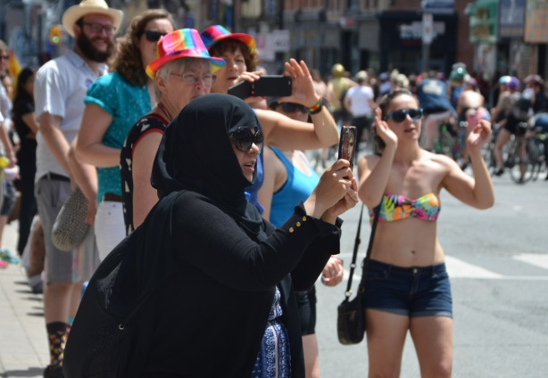 a muslim woman in a black head scarf takes pictures on her phone at a dyke march. a woman in a bikini top is clapping as she walks toward the camera