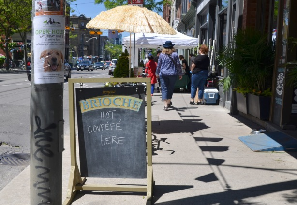 a blackboard sign on the sidewalk in front of Brioche restaurant that says we serve Covfefe. People walking on the sidewalk,
