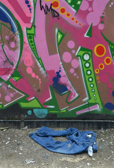 a pair of blue jeans are lying on the ground at the foot of a wall that has pink and green street art on it.