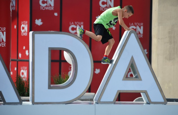 a young boy is leaping from the D of the 3D Canada 150 sign in front of the CN Tower, and is leaping onto the top of the A. His hands are on the top of the A, one foot is one the side of the A and the other foot is near the top of the D
