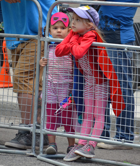 two kids stand behind metal barricades while waiting for the parade to begin