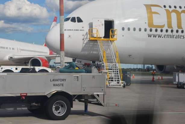 truck with the words lavatory waste is parked beside a large aircraft that has just unloaded