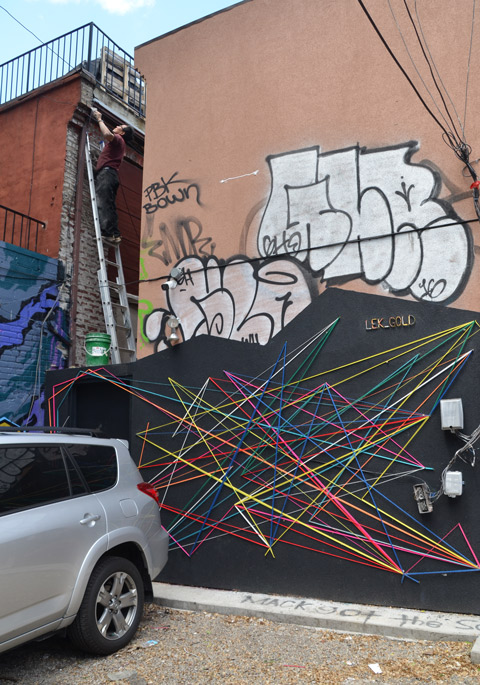 a man on a lddder, a car parked, multi coloured strings used to make art by stretching it between nails on an outside wall.