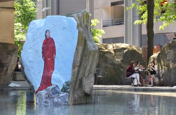 photograph or painting of a woman in red standing on a rock, directly onto the surface of a large rock in a shallow pool of water