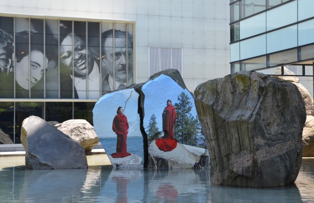 photograph or painting of a woman in red standing on a rock, directly onto the surface of a large rock in a shallow pool of water outside Ryerson Image Center, three large black and white photographs of people's heads are above and behind the artwork