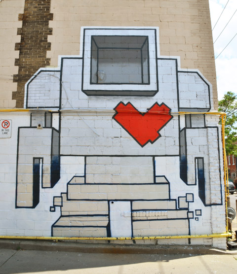 large lovebot, two storeys high, painted on the side of a building.