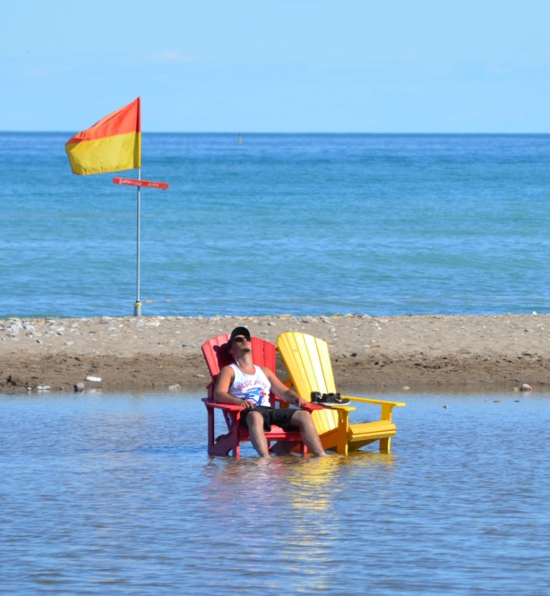 a man sits on a red Muskoka chair in the flooded part of Woodbine beach. A red and yellow flag flies behind him.