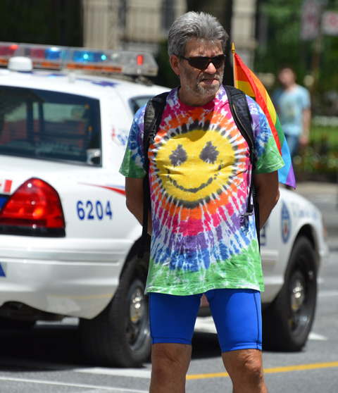 a middel aged man in a tie dyed shirt with a big happy face in the middle of it, stands by a police car as he watches the dyke march