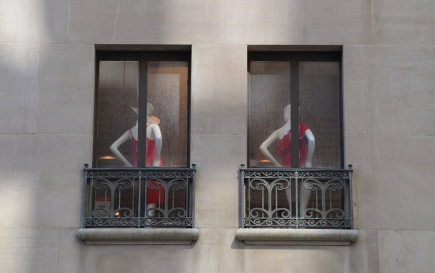 two mannequins with their backs to two windows, both dressed in red clothes