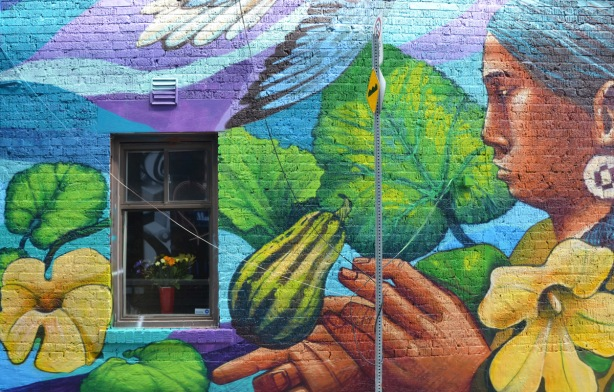 part of a larger mural on a wall with a window, a large painting of a woman appears to be looking at the window, a melon or gourd is in the mural too