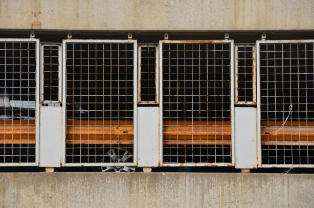 metal grille, part of a barricade along the side of a parking structure, rusted,