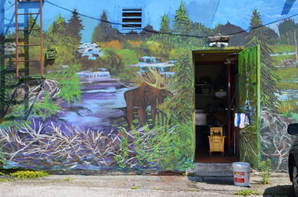 back of restaurant with open door. Ikki Sushi restaurant covered with a mural with scenes of Canadian flora and fauna, inside of door is painted too