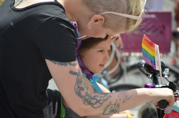 a mother leans over her young daughter who is sitting in front of her on a bike, Small rainbow flag is on the handlebars