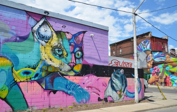 large colourful murals in pinks and blues of a cat reaching a paw out towards a mouse, in the background is antoher mural of a woman playing a guitar. Mural is by Jonny Cakes and sewp