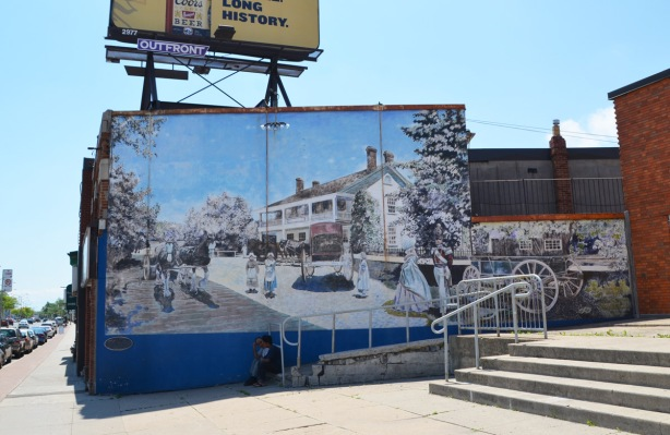 mural depicting the Half Way House, an old inn that used to be at the corner of Kingston Road and Midland. Two men are sitting on the stairs in front of the mural