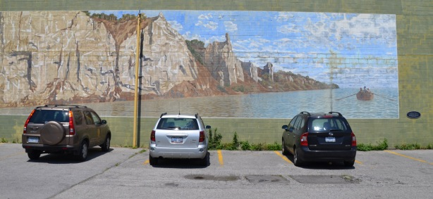 Three cars are parked in front of a large mural of the Scarborough Bluffs, there is a small row boat on Lake Ontario in front of the cliffs.