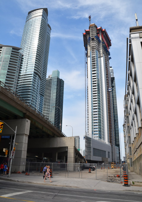 construction of a tall condo beside the gardiner expressway. The bottom of the condo is a wedge shape to maximize the space available