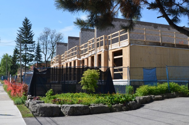 a row of townhouses being built, the lower floors are framed with plywood, the upper storey hasn't been started yet.
