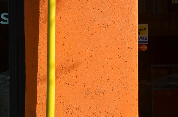 bright yellow pipe against a bright orange wall, with shadow.