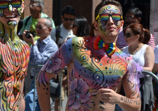 two men with a lot of bodypaint of rainbows and flowers as well some sparkly bits