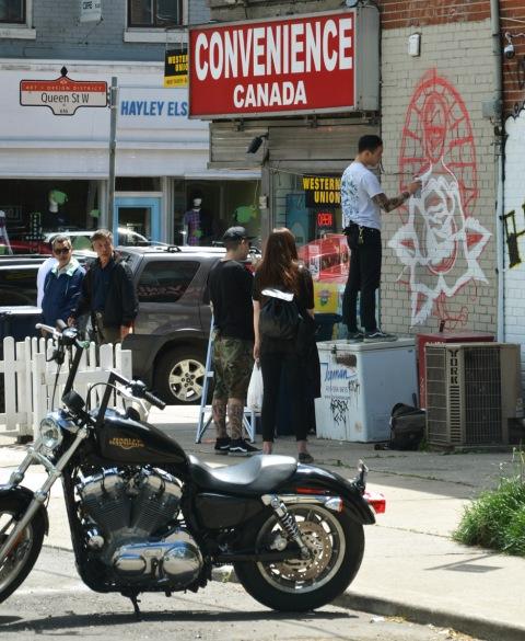 motorcycle in the foreground, a man painting a white outline of a rose as part of a mural on the side of Canada Convenience store on Queen West, a few people watching him paint