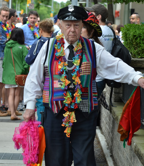 an older man is standing on the sidewalk, wearing a police cap and a patchwork vest in rainbow colours with all kinds of different fabrics, busy, bright,