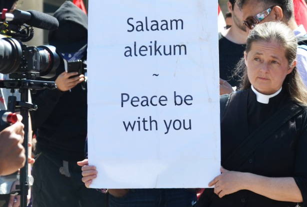 a woman in a priests collar on, holding a sign that says salaam aleikum peace be with you, being photographed and filmed by TV cameras
