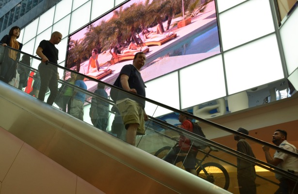 people riding down the escalator at the Eaton Centre, a large screen is playing a slideshow of summer pictures as part of an advertising campaign.
